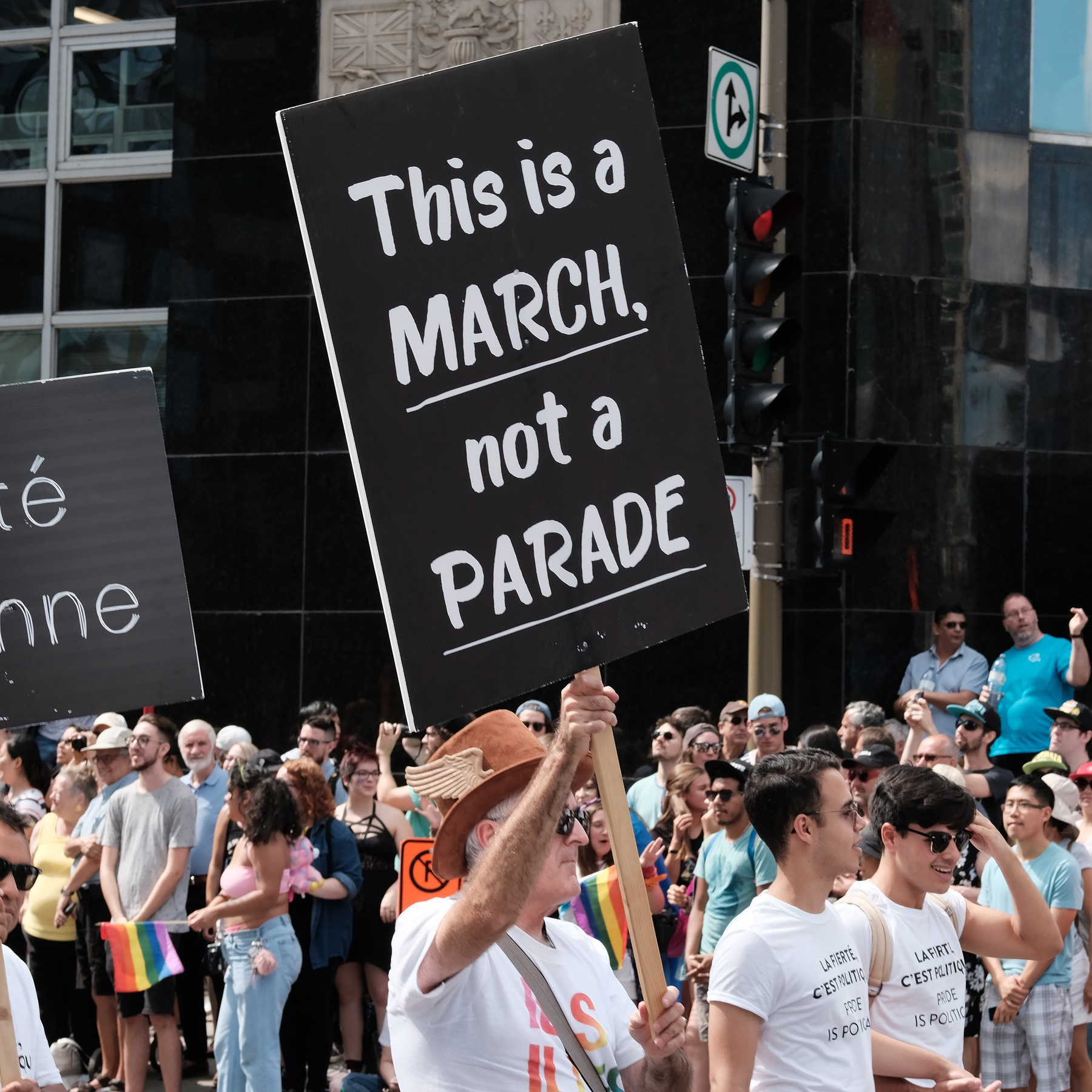 An elderly man holds a sign that says 'This is a march, not a parade'