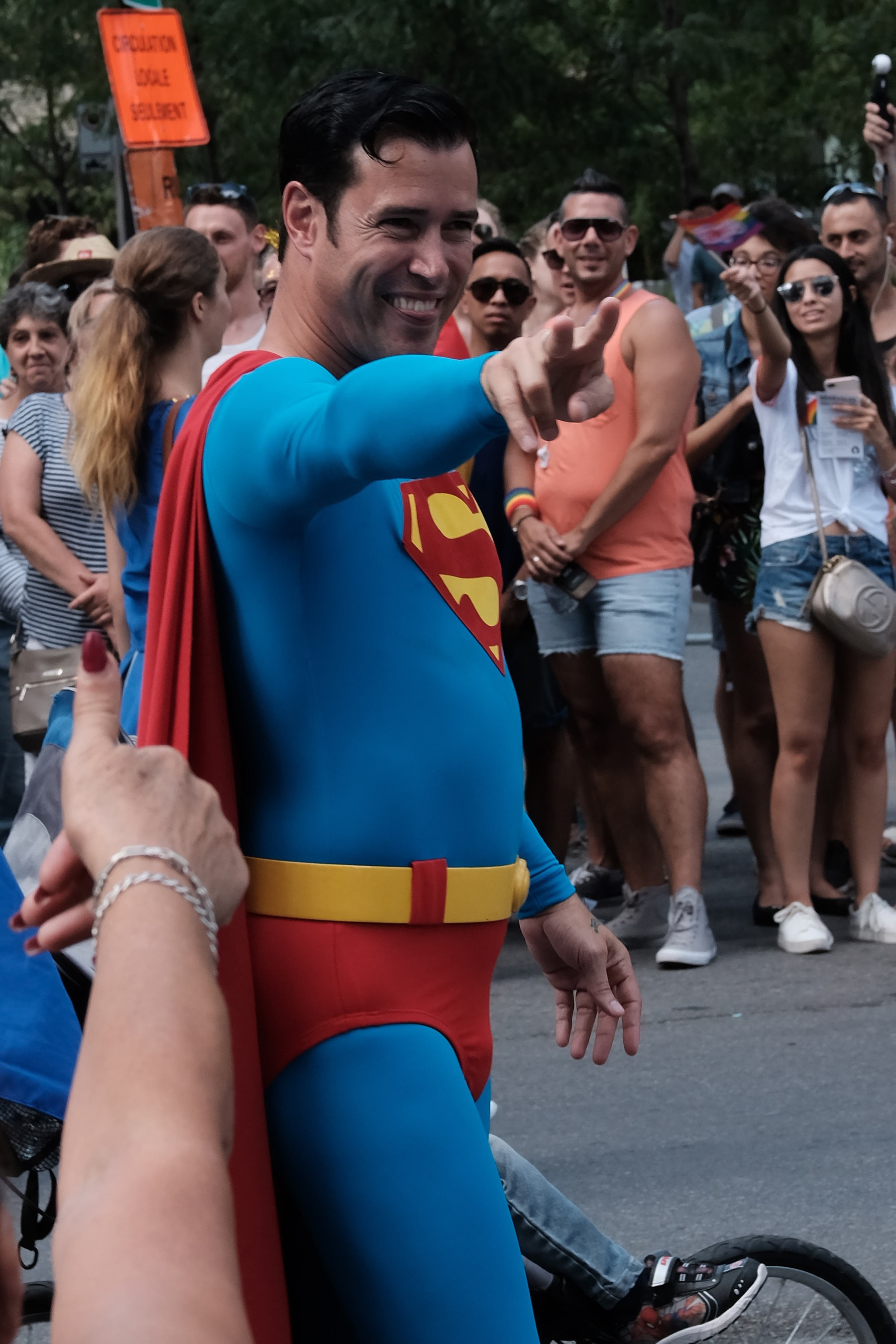 A man dressed up as superman waves at the crowd