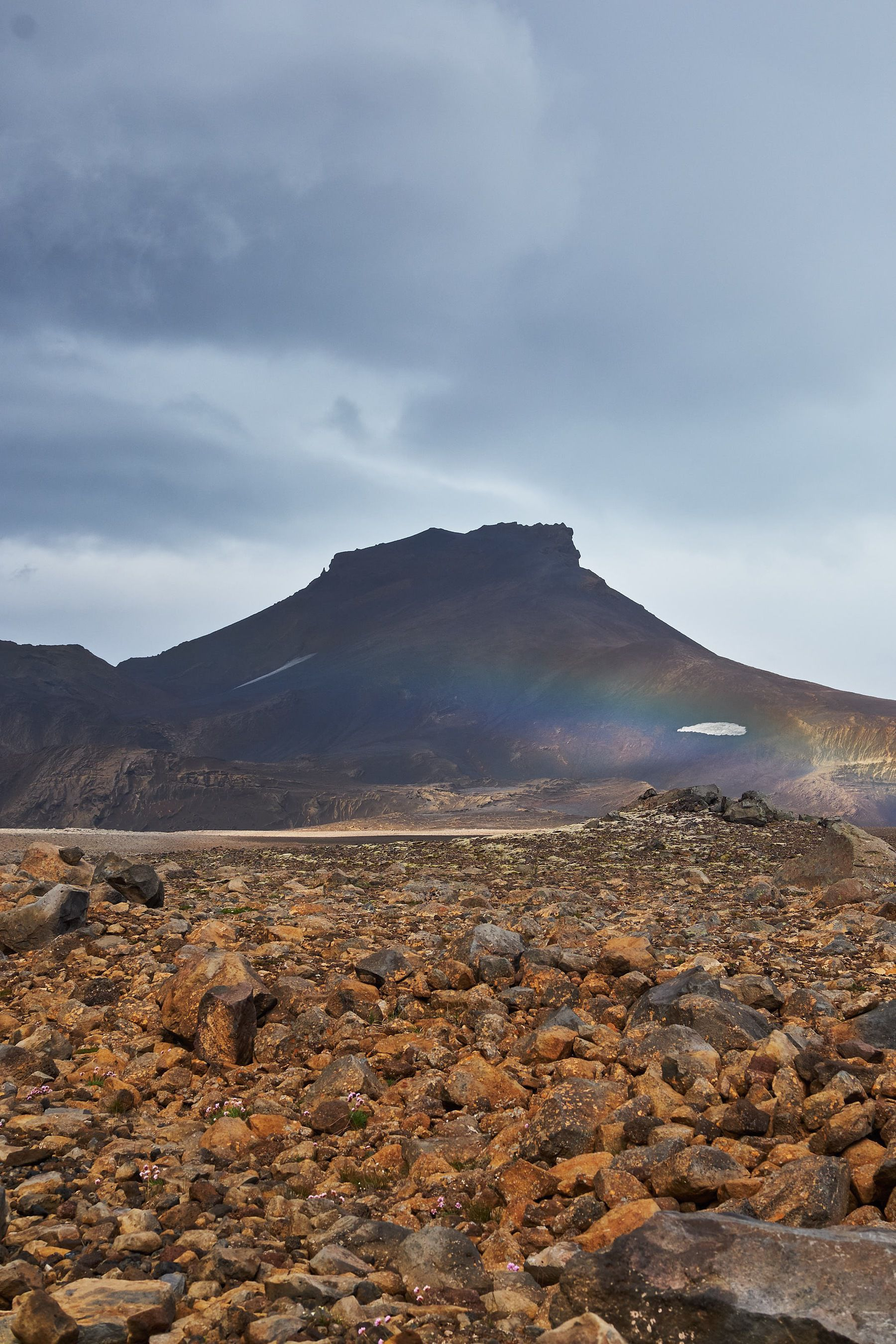 Barren highlands. A mountain is centred in the background, partially covered by a rainbow.