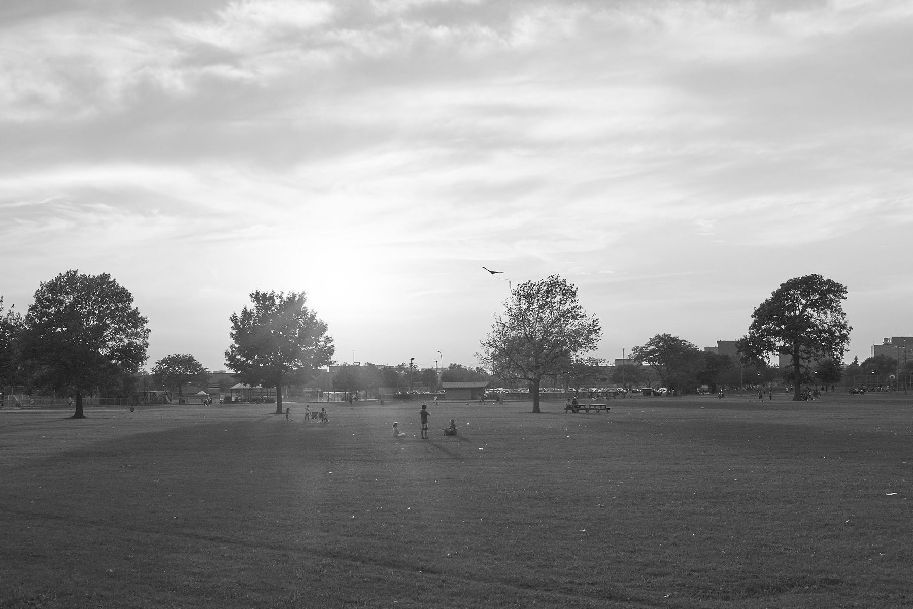 Children fly a kite as the sun sets of Parc Jarry.