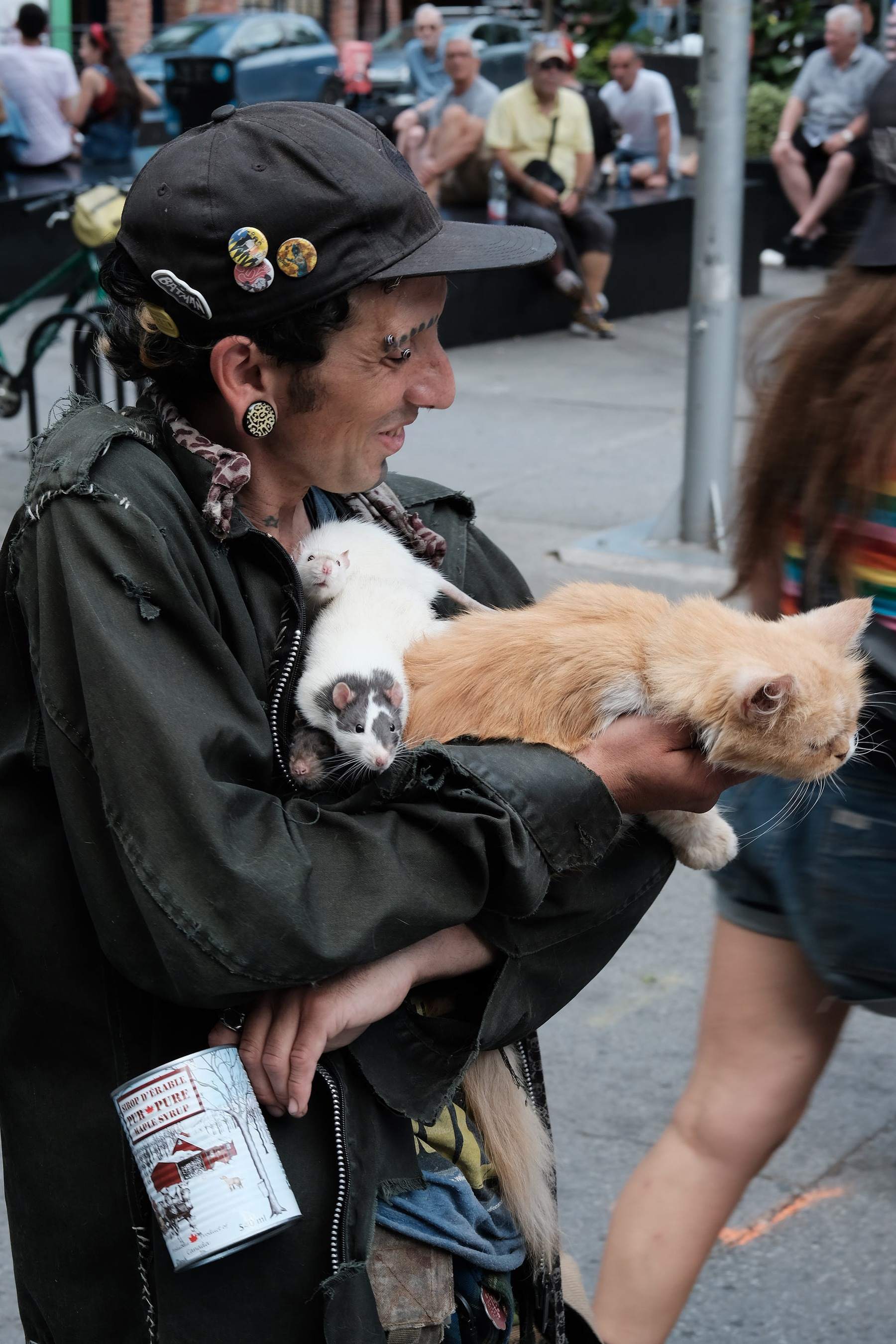 A man holding three pet rats and a cat is busking with an empty maple syrup can
