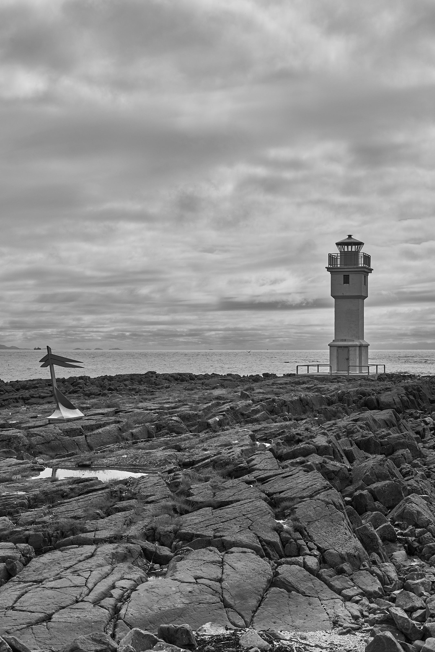 The old lighthouse against a cloudy sky with a rocky beach in the foreground