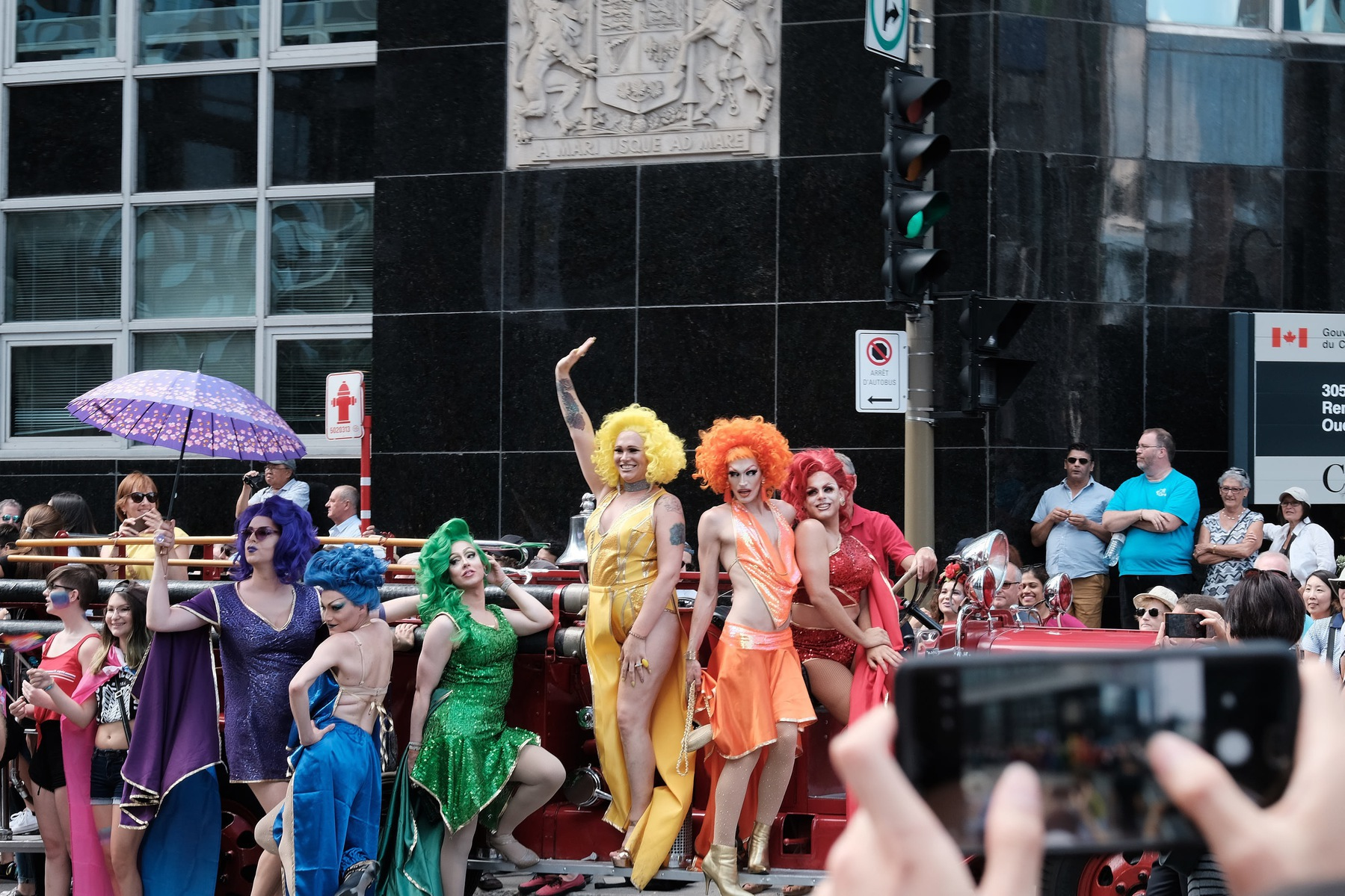 A crowd of drag queens post on an antique fire engine. A hand holding a phone is in the foreground, taking a picture.