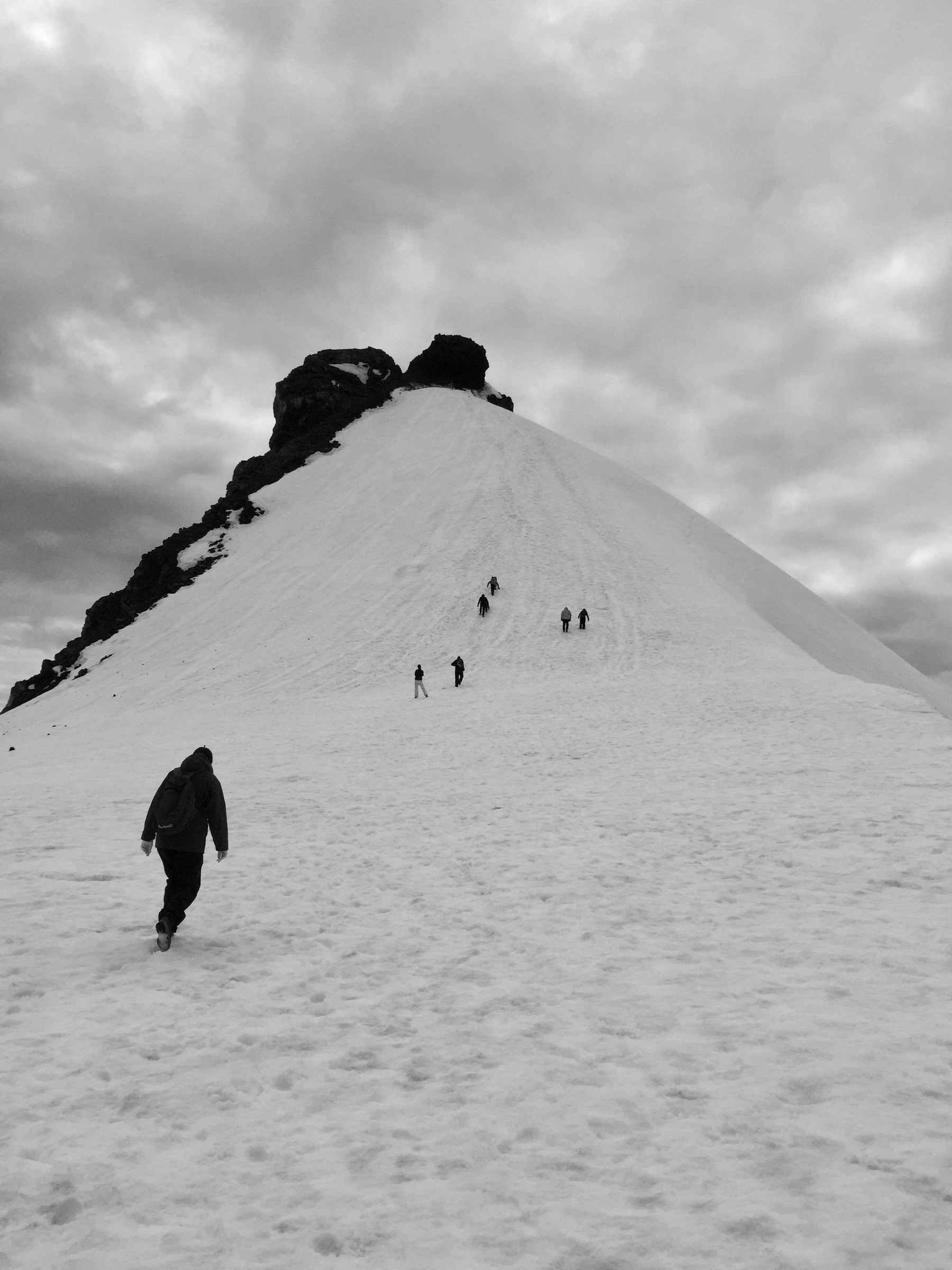 A group of people walk up the peak