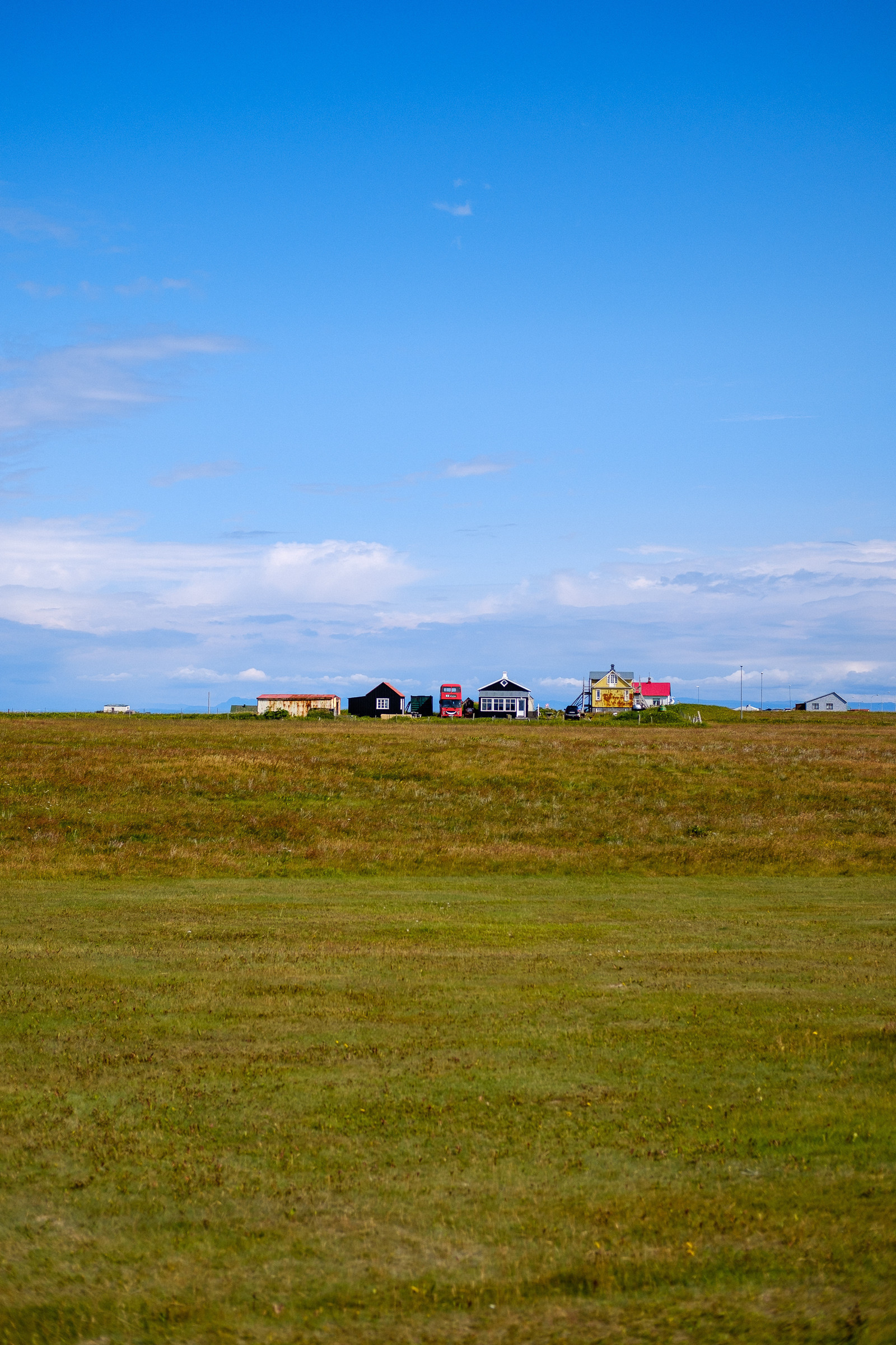 A double-decker tour bus parked by an old Icelandic farm