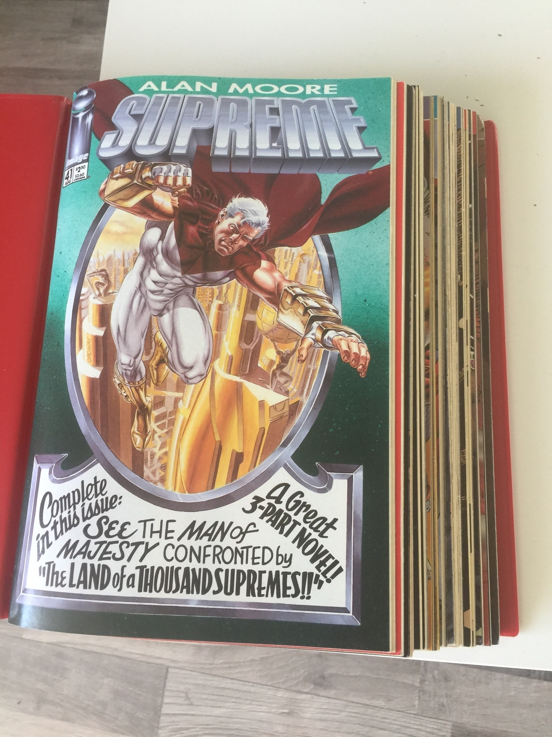"""A binder containing a stack of comics. The topmost one is titled """"Alan Moore: Supreme"""""""
